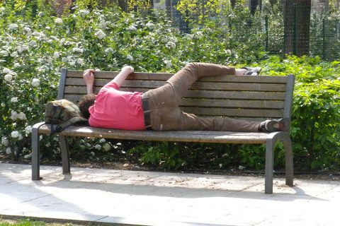 teen napping on park bench